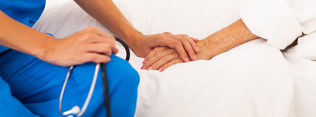 nurse holding elderly patients hand